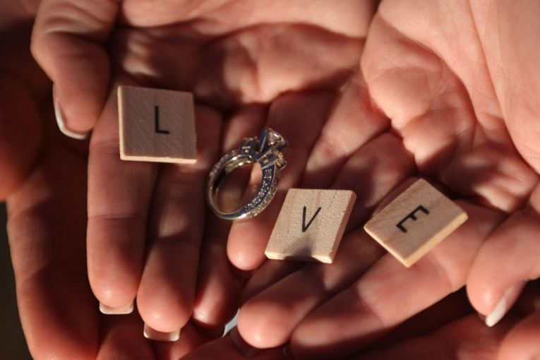 Dices with letters L, V and E and a diamond ring as letter O forming the word LOVE of a couple's hands