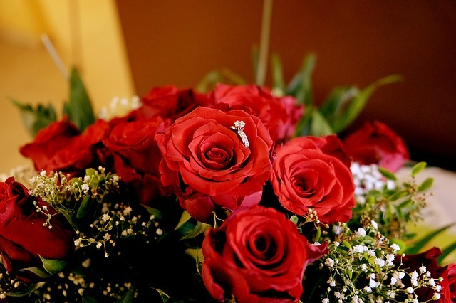 an engagement ring on a bouquet of red roses